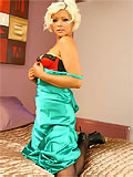 cute blonde in pinup style wearing in black stockings and colour corset under her green evening dress