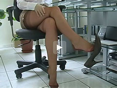 Secretary`s shoe dangling in miniskirt and brown seamed nylons!